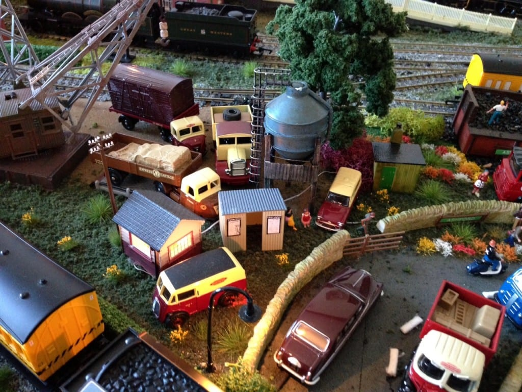 shacks, a water tower, and trucks on the night time model train layout