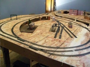 Miniature houses and model train tracks on a wooden table.