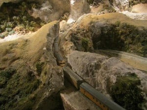 The model train passes through a narrow passage between two rocky mountain walls.