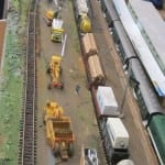 Construction vehicles next to the model train.