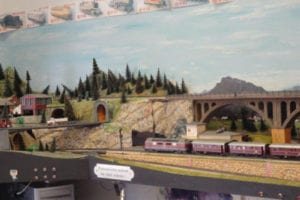 Tunnel under a hill of pine trees with trucks and model train.