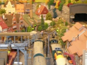Model train moving through the city with railway signals.