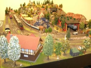 Model railroad with the houses in a backdrop of warm sunlight.